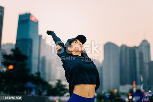istock Young Asian woman exercising and stretching arms overhead outdoors against urban city skyline 1134281898