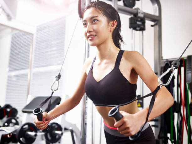 young asian woman exercising in gym using equipment stock photo