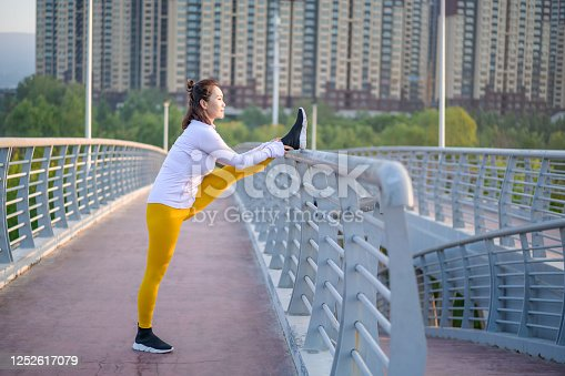 Young Asian woman exercising in the city street