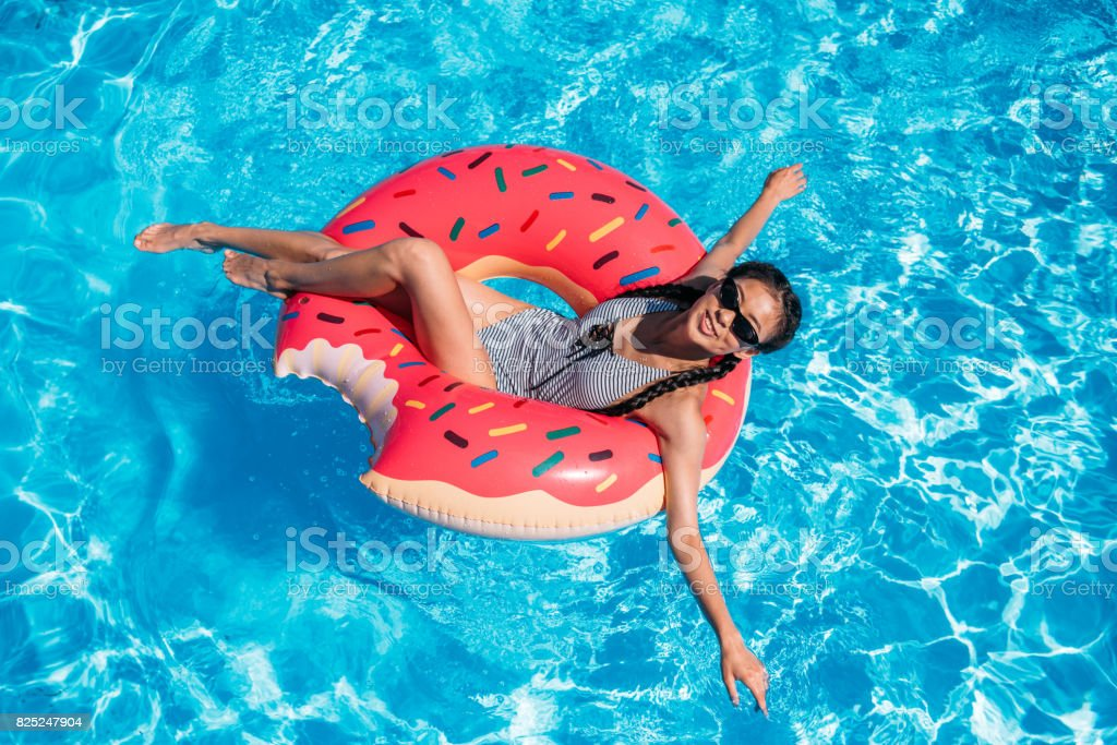Young asian woman floating on inflatable donut in swimming pool stock photo