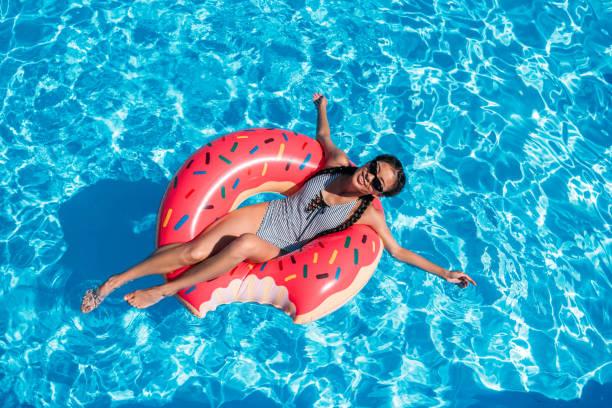 Jovem mulher asiática flutuando sobre donut inflável na piscina - foto de acervo