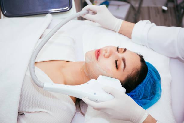 Junge Asiatin IPL und Laser Behandlung von Kosmetikerin bei Beauty-Klinik zu bekommen. – Foto
