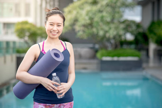 Young Asian woman hand holding purple yoga mat at swimming pool Young Asian woman hand holding purple yoga mat and water bottle at swimming pool, outdoor exercise and healthy lifestyle concepts yoga instructor stock pictures, royalty-free photos & images