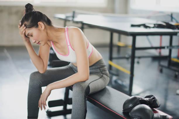 junge asiatische frau haben kopfschmerzen beim training im fitnessstudio, der hintergrund ist tischtennis. unfalltraining bei fitness, muskelschmerzkonzept. - mit muskelkater trainieren stock-fotos und bilder