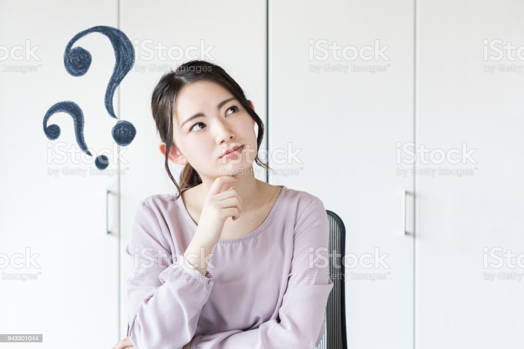 Young asian woman having questions. stock photo