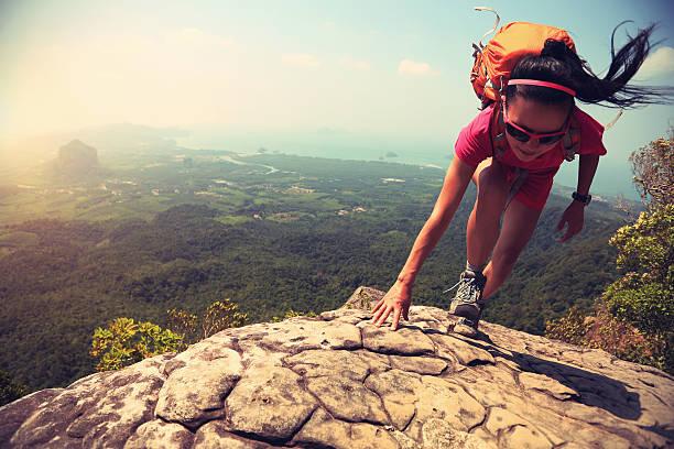 Joven mujer asiática excursionistas escalada en roca en el pico de la montaña desde acantilado - foto de stock