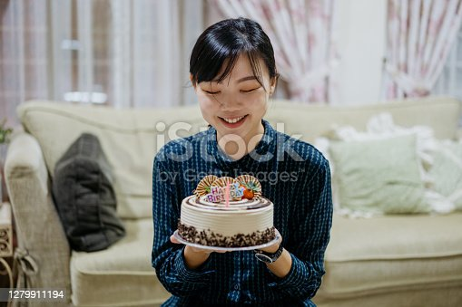 Young asian woman holding a birthday cake in living room