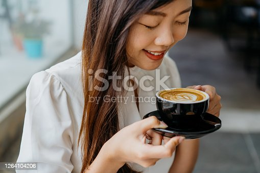 A shot of young asian woman holding a cup of coffee with saucer, enjoying a quiet moment in cafe