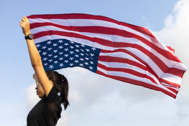 a young asian woman holding american flag on blue sky background - family 4th of july zdjęcia i obrazy z banku zdjęć