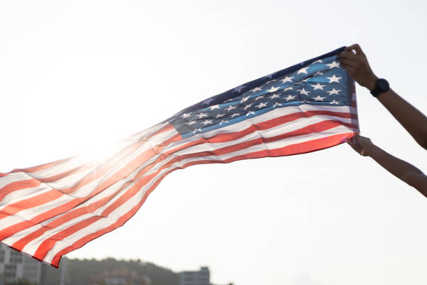 a young asian woman holding american flag with sun flare. - family 4th of july zdjęcia i obrazy z banku zdjęć