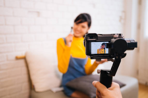 Young Asian woman holding cosmetics brush while recording a video with professional camera stock photo