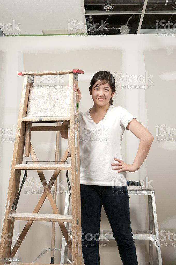 Young Asian Woman Holding Ladder in Unfinished Room stock photo