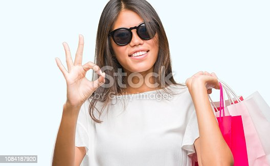 Young asian woman holding shopping bags on sales over isolated background doing ok sign with fingers, excellent symbol