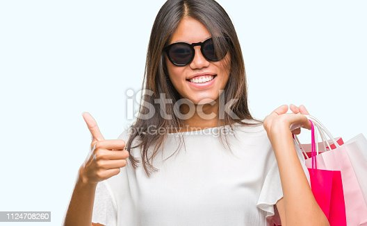 Young asian woman holding shopping bags on sales over isolated background happy with big smile doing ok sign, thumb up with fingers, excellent sign