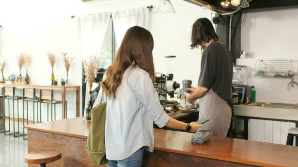 Young asian woman holding smart phone for paying contactless at coffee shop, cafe background, Small business financial and contactless payment concept stock photo