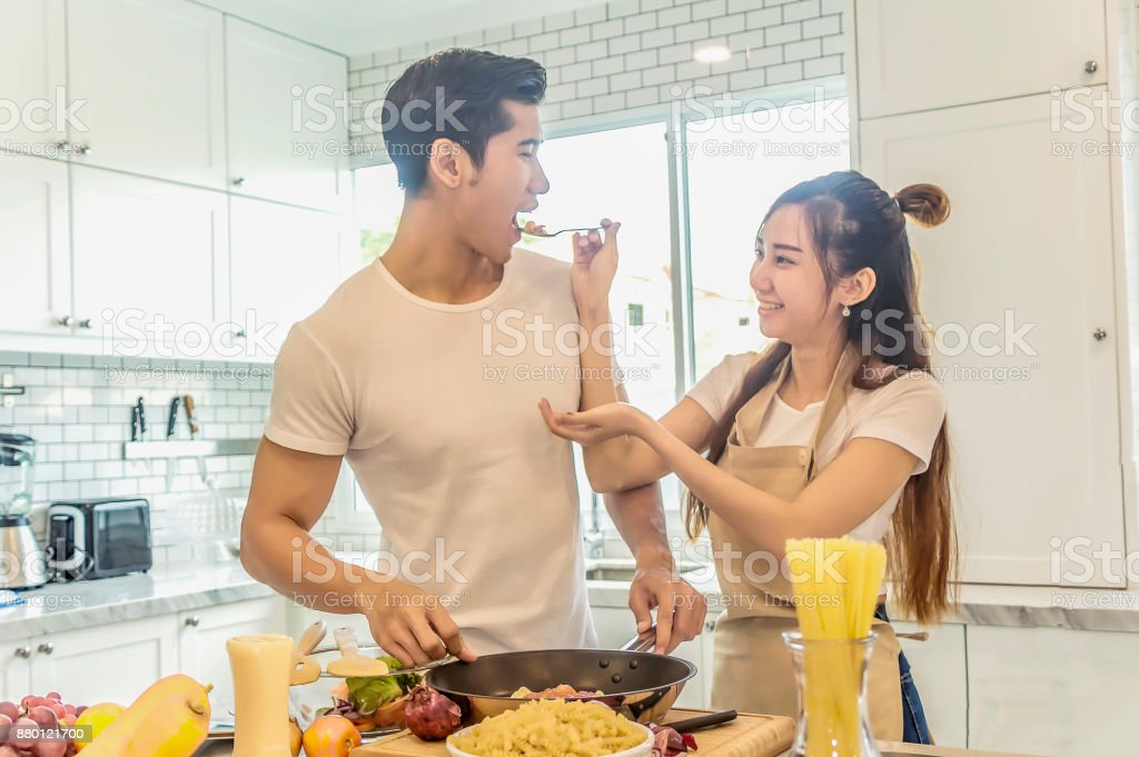 Young asian woman holding spaghetti to man eating each for cooking dinner.Sweet couple home kitchen cooking lover concept. stock photo