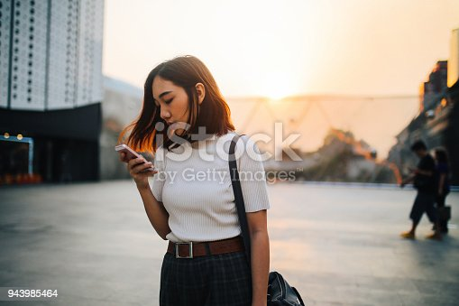 Vintage colored portrait of a young Asian woman, relaxing and texting on the cellphone at the busy Siam station of the Skytrain, next to popular shopping malls and restaurants. She is wearing casual clothing, drinking a juice to refresh.