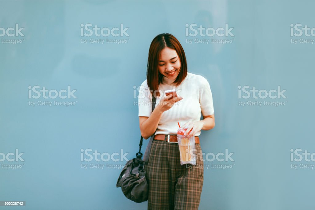 Young Asian woman in Bangkok downtown district, taking a break, texting on the cell while having a drink zbiór zdjęć royalty-free