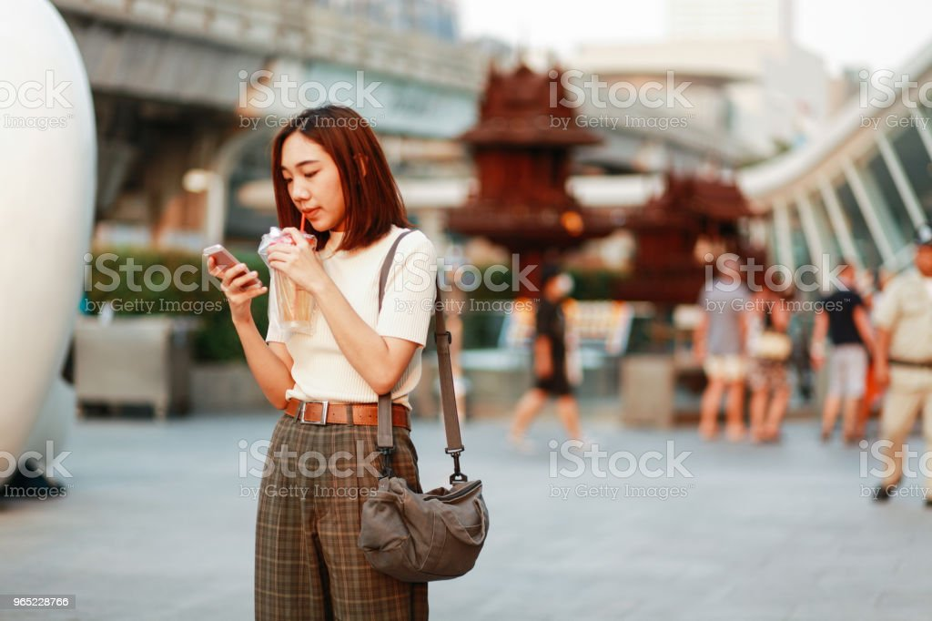 Young Asian woman in Bangkok downtown district, taking a break, texting on the cell while having a drink royalty-free stock photo