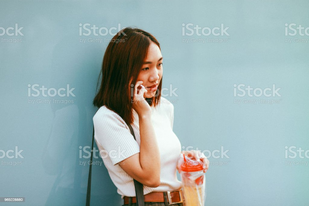Young Asian woman in Bangkok leaning against the turquoise wall, taking a break, talking on the cellphone while having a drink zbiór zdjęć royalty-free