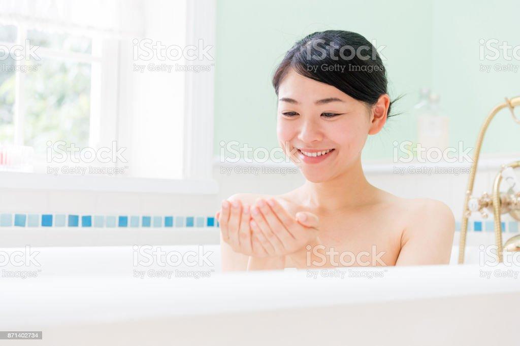 浴室で若いアジア女性 ストックフォト