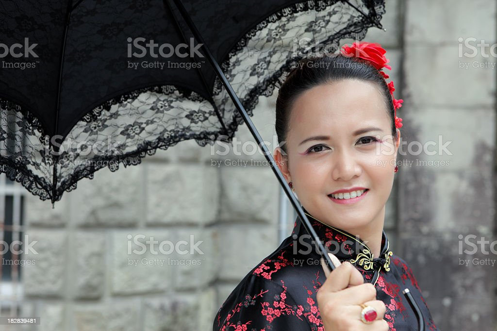 Junge asiatische chinesische Frau in einem schwarzen Kleid holding Regenschirm Lizenzfreies stock-foto