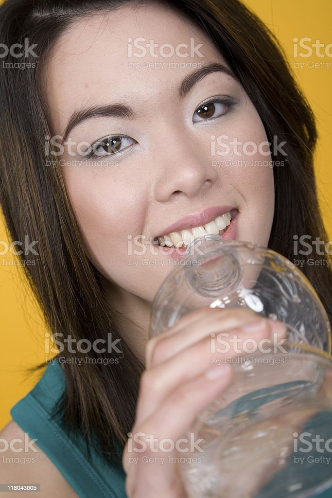 Young Asian Woman In Front Of Yellow Background royalty-free stock photo