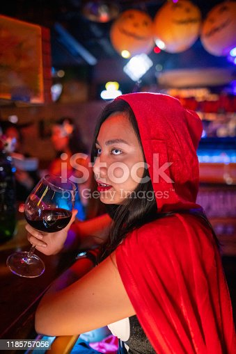 Young Asian woman in Halloween costume drinking red wine in night club