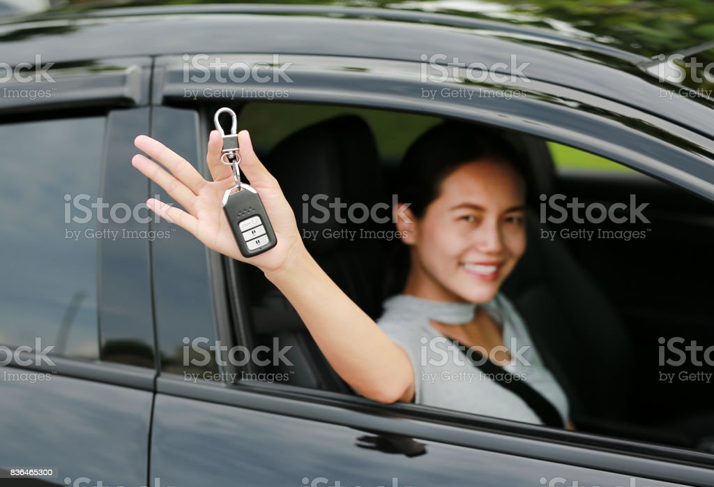 Young asian woman inside a car, hold the key out from the window. Focus at a key hanging at her hand. stock photo