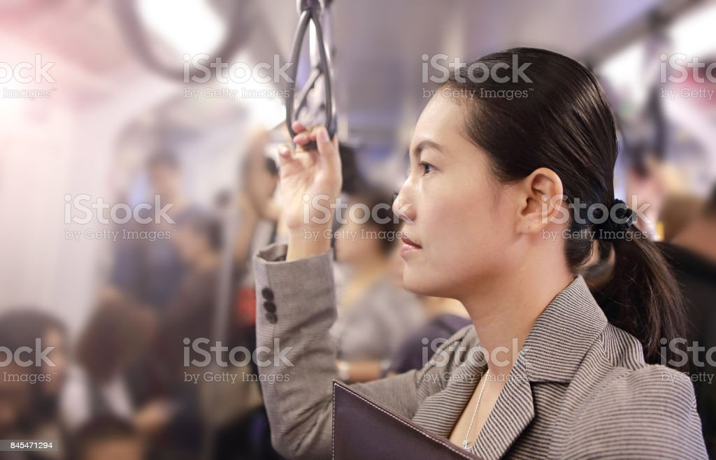 Young asian woman inside BTS (Bangkok Mass Transit System), the public transportation in Bangkok, Thailand. stock photo