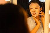 若いアジアの女性は、彼女の顔に顔のシートマスクを適用し、バスルームで彼女の反射を見ています