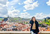 single young Asian woman laughing at Cesky Krumlov town, Czech Republic