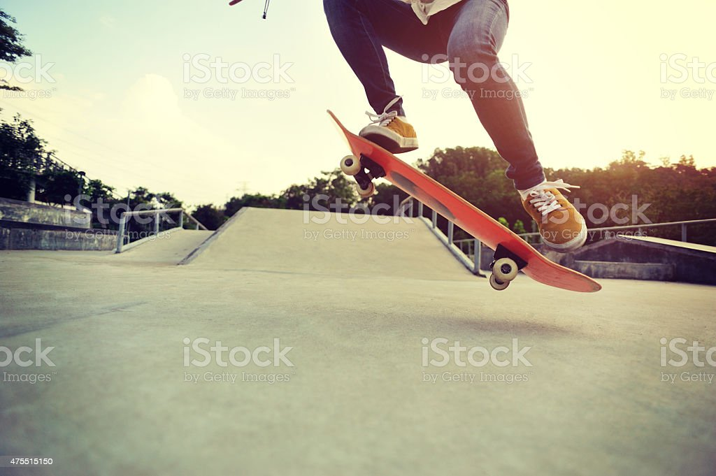 young asian woman legs skateboarding at skatepark stock photo
