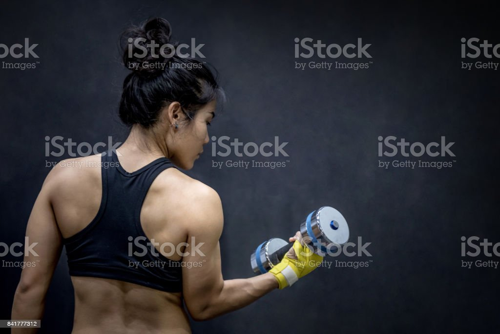 Young Asian woman lifting dumbbell in weight training fitness gym stock photo
