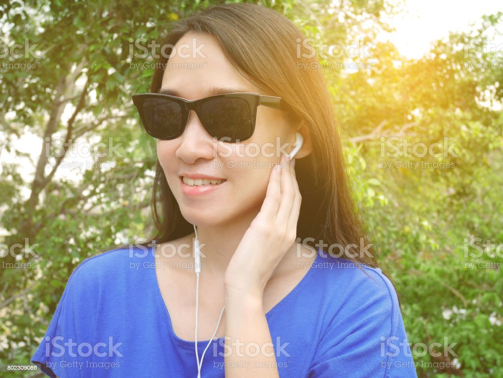 Young asian woman listening to music stock photo