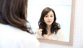 鏡を見て若いアジアの女性。