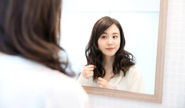 鏡を見て若いアジアの女性。 - 美容室 ストックフォトと画像