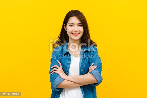 867955978 istock photo Young Asian woman looking at camera and smiling, arms crossed in hand studio shot isolated on yellow background. 1214079829