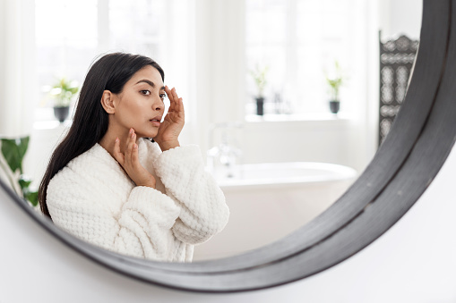 Skincare and beauty concept. Side portrait view of young asian woman touching healthy facial skin, checking acne. Female in white bathrobe looking at mirror, spending morning in bathroom