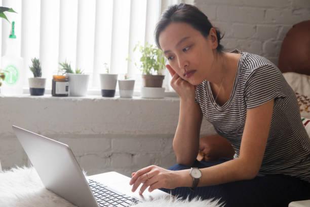 Junge asiatische Frau auf der Suche online für Arbeit ernsten Ausdruck – Foto