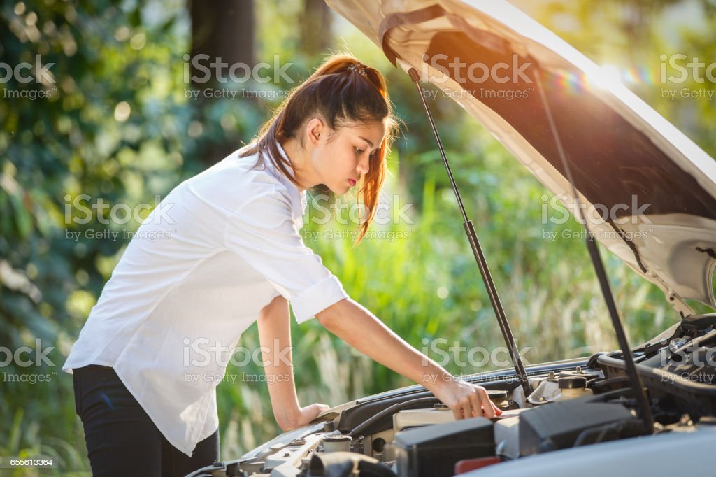 Young asian woman looks under the hood of a broken car. stock photo