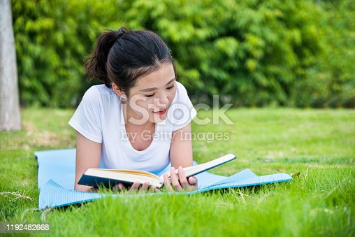 862602714 istock photo Young asian woman lying on green grass and reading a book 1192482668