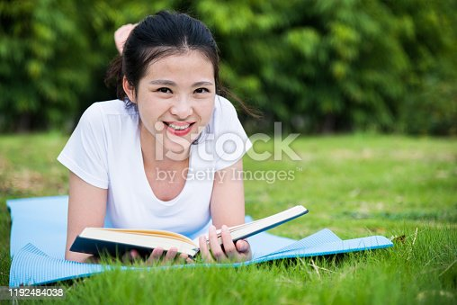 862602714 istock photo Young asian woman lying on green grass and reading a book 1192484038