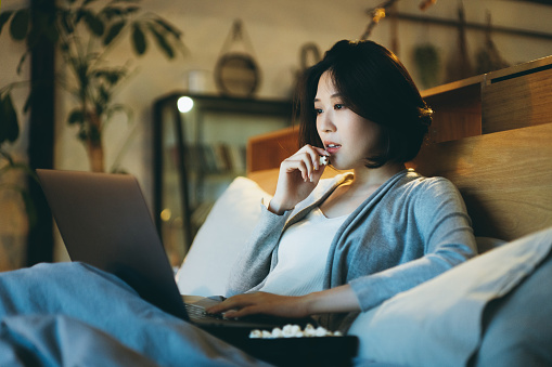 Young Asian woman lying on the bed enjoying the weekend, watching movie on laptop and eating popcorn at home in the evening