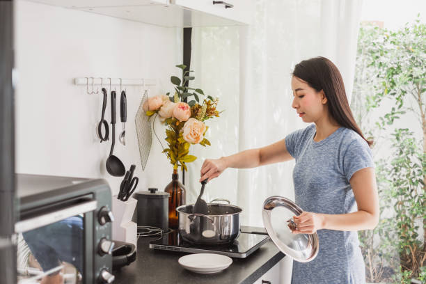 Young Asian woman making healthy food  in kitchen at home Young Asian woman making healthy food  in kitchen at home southeast asian ethnicity stock pictures, royalty-free photos & images