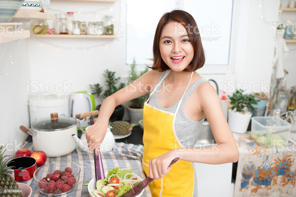 Young asian woman making salad in kitchen smiling stock photo