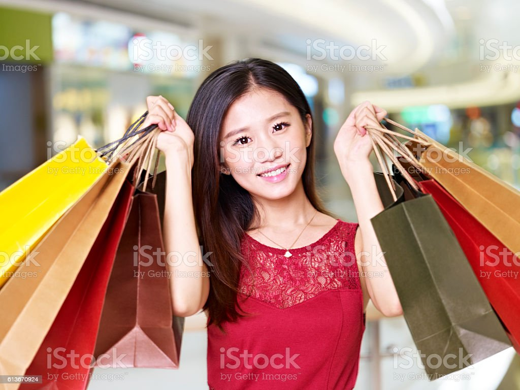young asian woman on shopping spree carrying paper bags walking in...