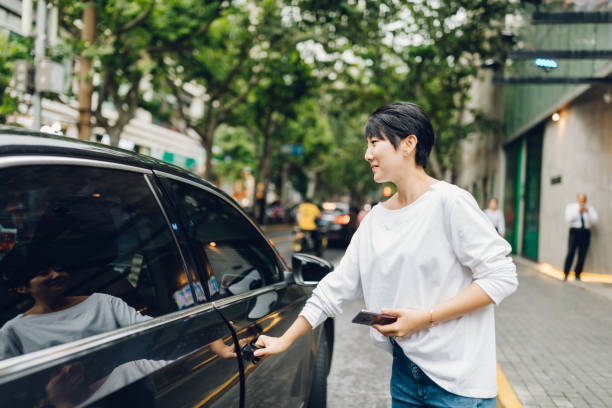 Young Asian woman ordering a taxi ride with mobile app on smartphone in the city. stock photo