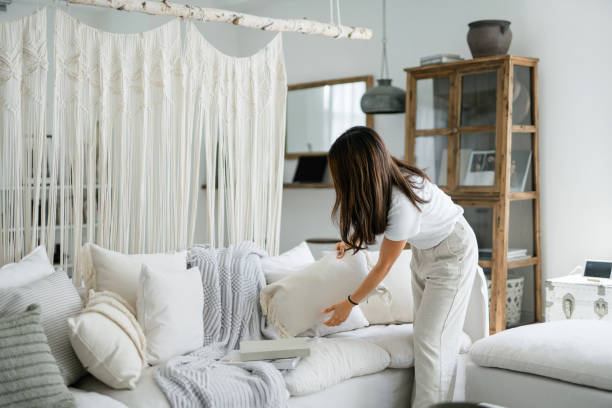 Young Asian woman organising and tidying up the cushions on the sofa in the living room at home