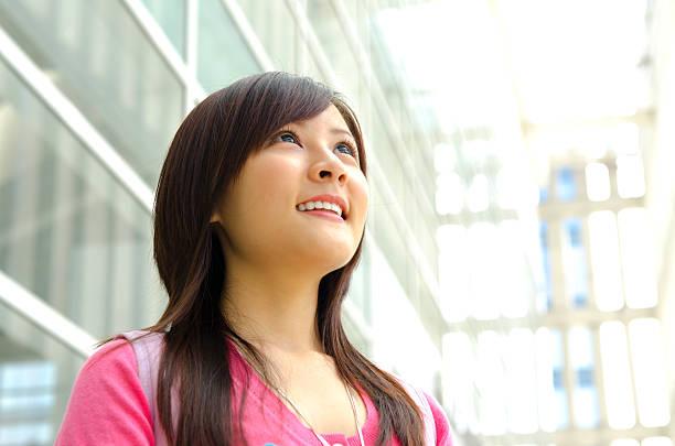 jovem mulher asiática, olhando para o céu ao ar livre, - vida de estudante - fotografias e filmes do acervo